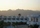 Фото туриста. отель в вечерних лучах солнца, позади - пустыня